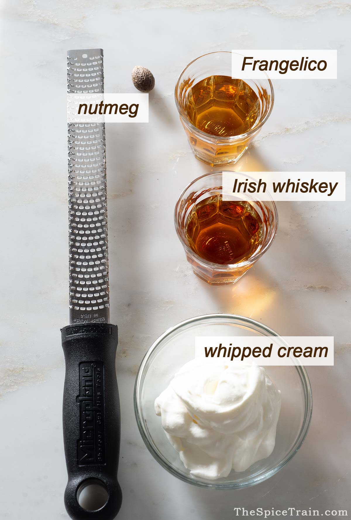Whiskey and Frangelico cocktail ingredients with a grater on a kitchen counter.