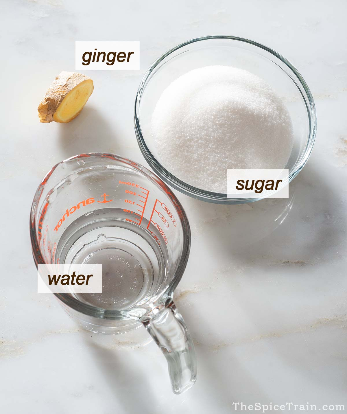 Ginger, sugar and water on a kitchen counter.
