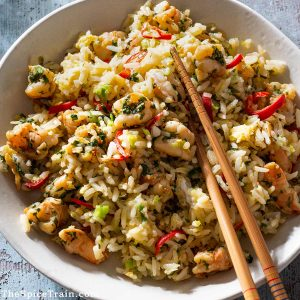 Fried rice with shrimp and chopsticks on a plate.