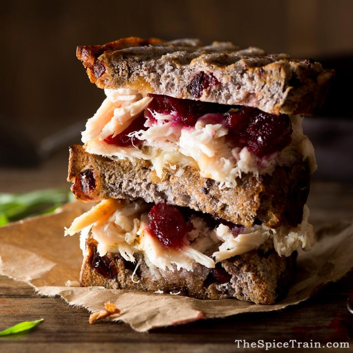 A stacked turkey cranberry grilled sandwich.