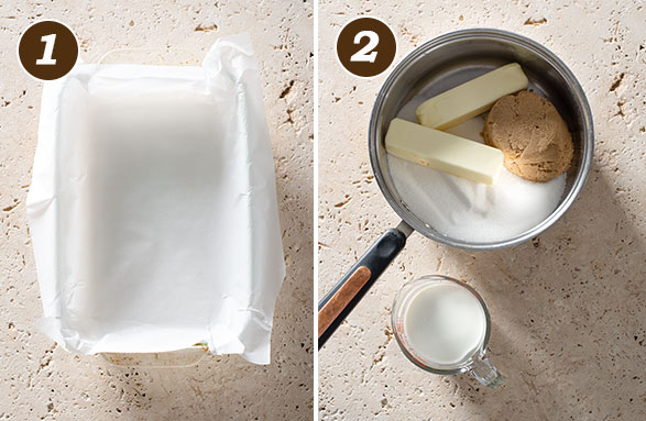 A rectangular glass baking pan lined with parchment paper and a pot with granulated sugar, brown sugar, butter and a measuring cup with cream next to it.