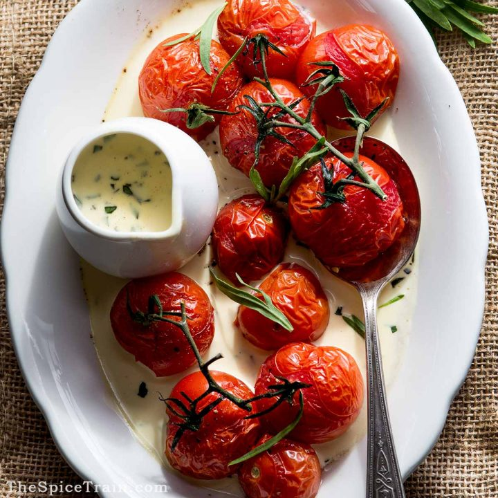A serving plate with roasted tomatoes and tarragon sauce.