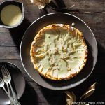 An apple tart drizzled with custard sauce on a wooden table in a fall afternoon setting.
