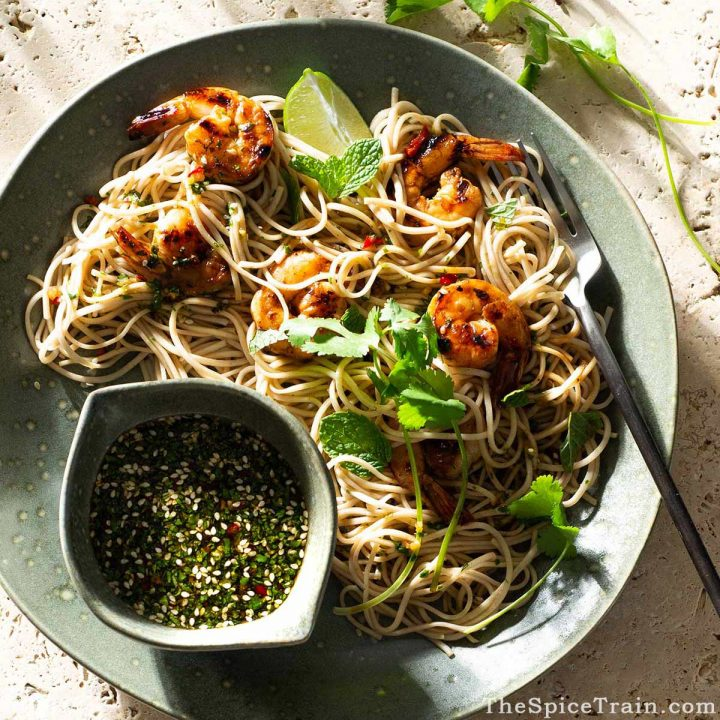 Asian noodle salad on a large plate with a dipping dish filled with dressing.