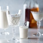 Glasses filled with Bourbon milk punch and a bottle of Bourbon in the background.