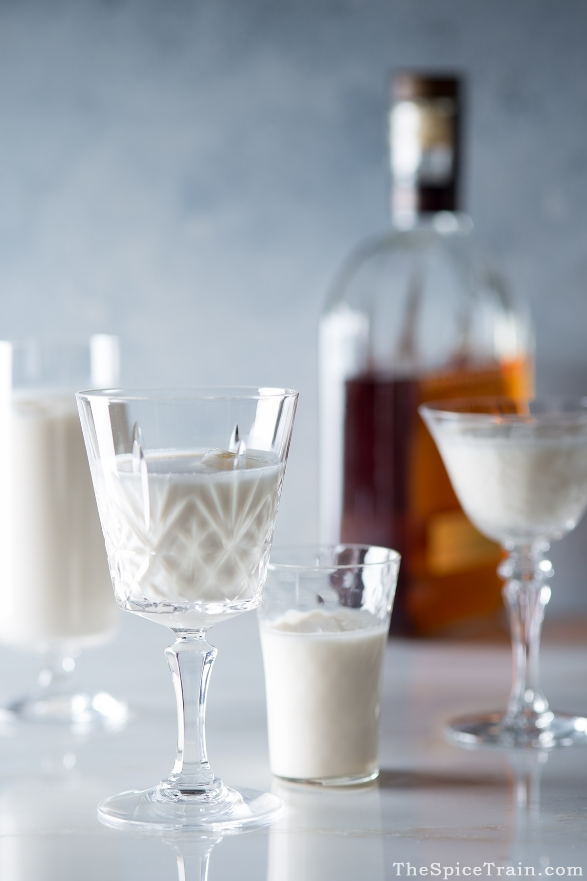 Glasses filled with Bourbon milk punch and a bottle of Bourbon.