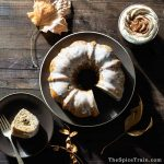 A glazed bundt cake with one slice cut out in a late afternoon fall setting with a cup of hot chocolate and whipped cream next to it.
