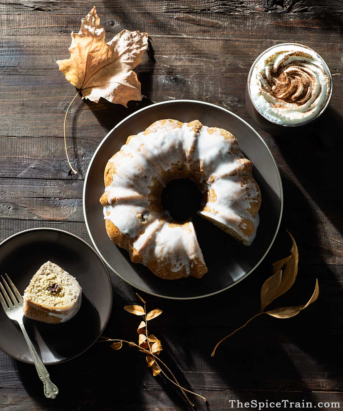 A glazed bundt cake with one cut out slice and a cup of hot chocolate.
