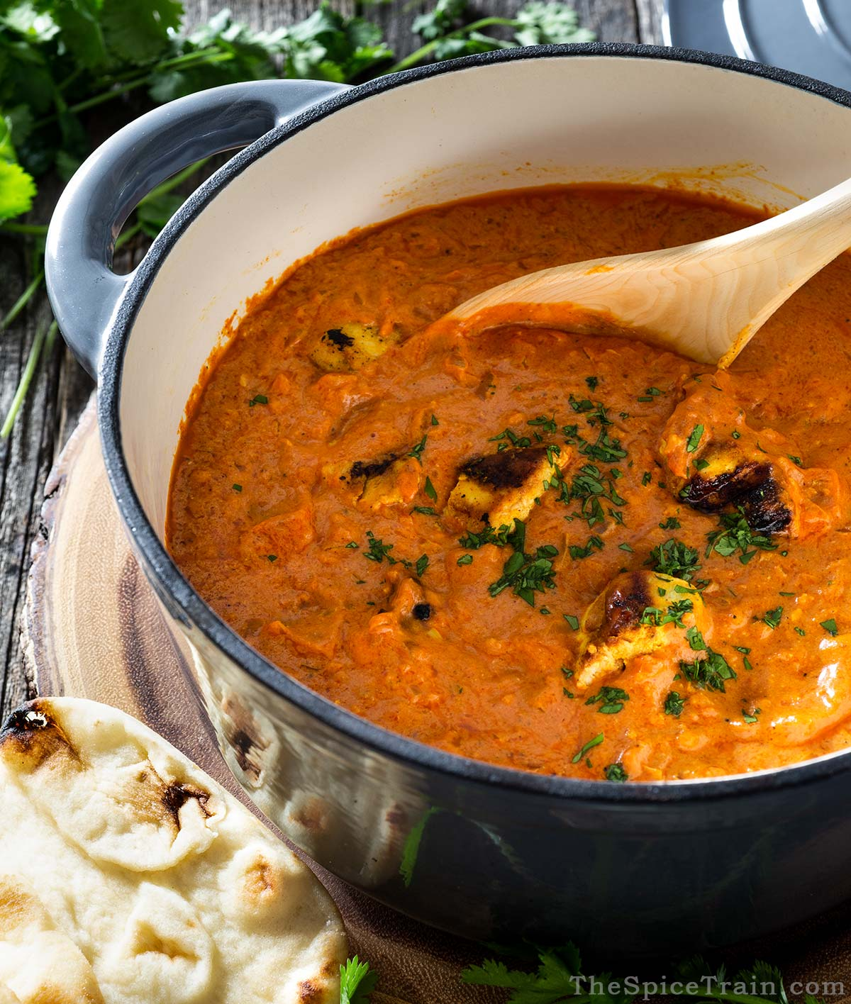 A Dutch oven filled with tikka masala curry, fresh cilantro and naan bread.