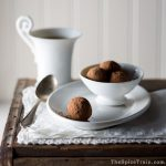 Chocolate truffles rolled in cocoa powder with a cup of coffee in the background.