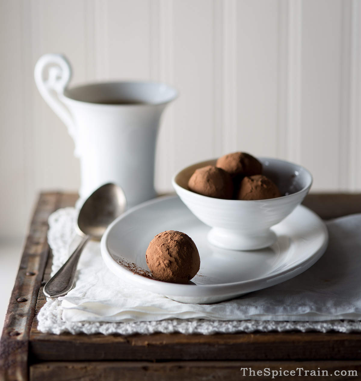 Chocolate truffles rolled in cocoa powder and a cup of coffee.