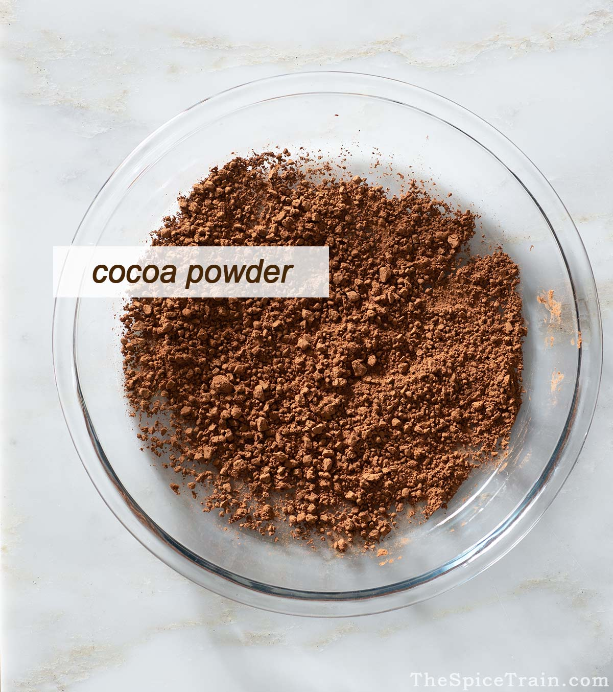 Cocoa powder in a glass pie dish.