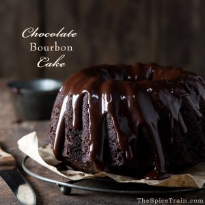 A chocolate bourbon bundt cake with freshly poured chocolate glaze on it.