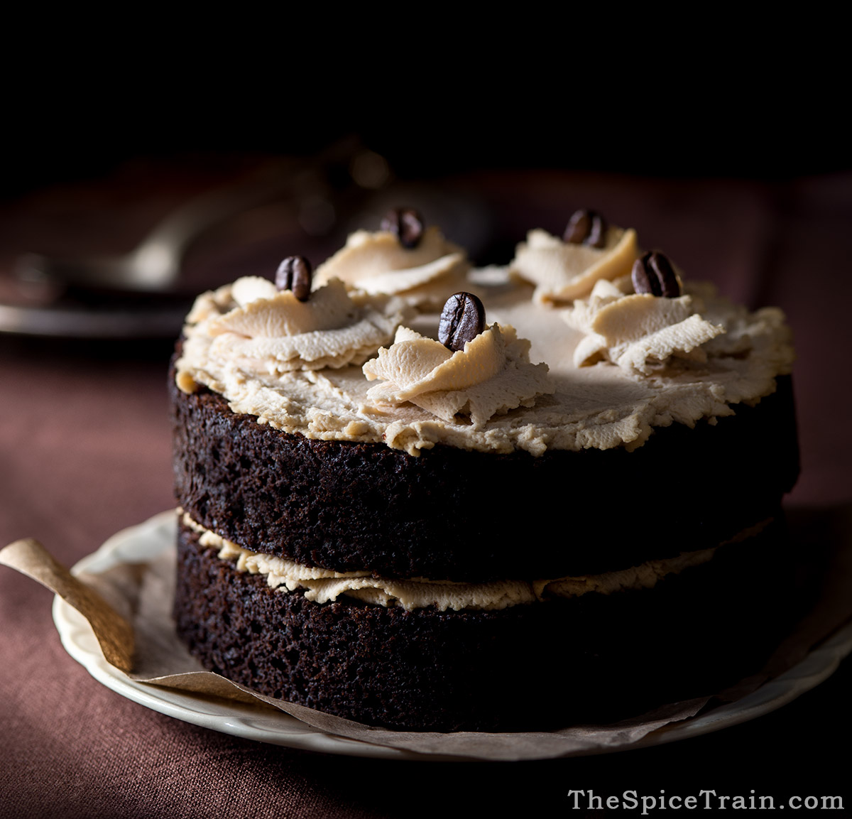A chocolate layer cake frosted with mascarpone frosting and decorated with coffee beans.