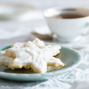 Glazed vanilla bean shortbread cookies on a small plate with a cup of tea in the background.