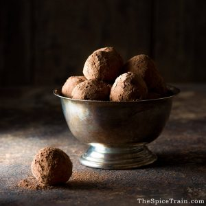 A metal bowl filled with chocolate truffles.