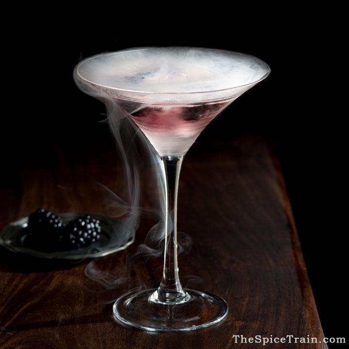 A tall, elegant glass filled with a bramble cocktail and smoke from dry ice.