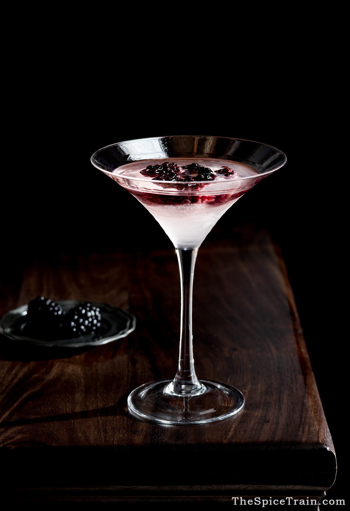 A tall, elegant glass filled with a bramble cocktail.