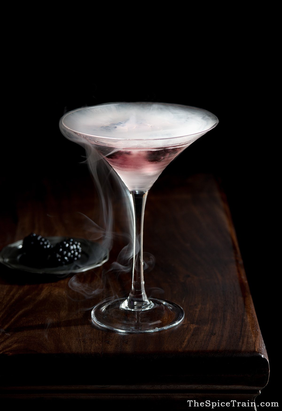 A glass filled with a bramble cocktail and smoke from dry ice.