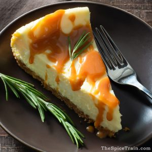 A cheesecake slice drizzled with caramel sauce and garnished with a sprig of fresh rosemary.