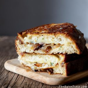Two grilled cheese sandwiches stacked on top of each other.