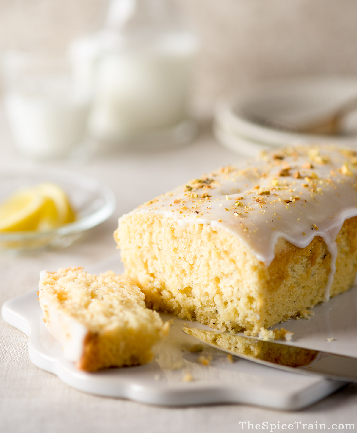 A lemon cardamom loaf cake with the first slice being cut on a ceramic cutting board.