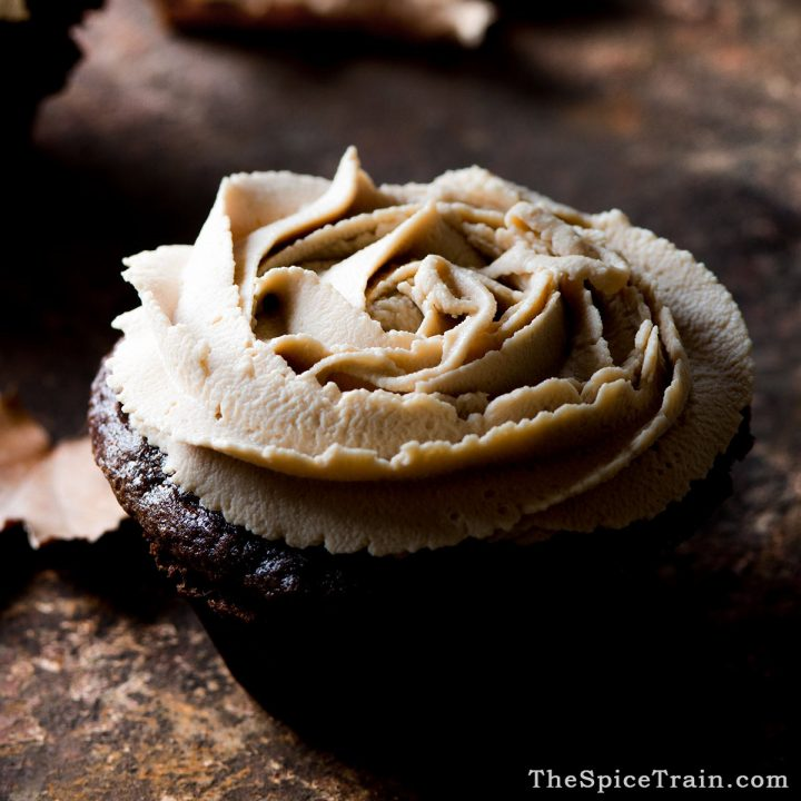 Closeup of a chocolate cupcake topped with piped maple mascarpone frosting.