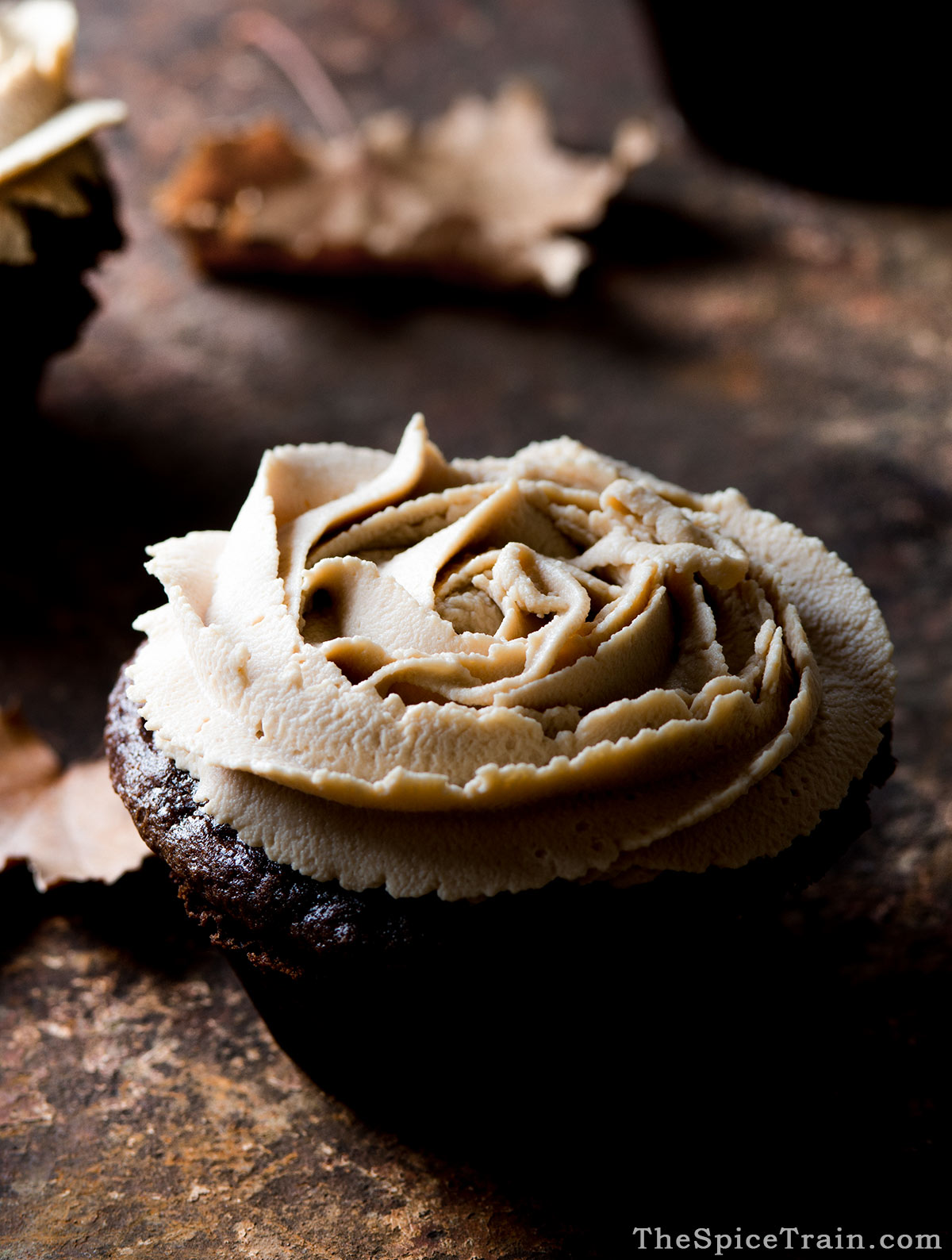 A chocolate cupcake topped with piped mascarpone frosting.