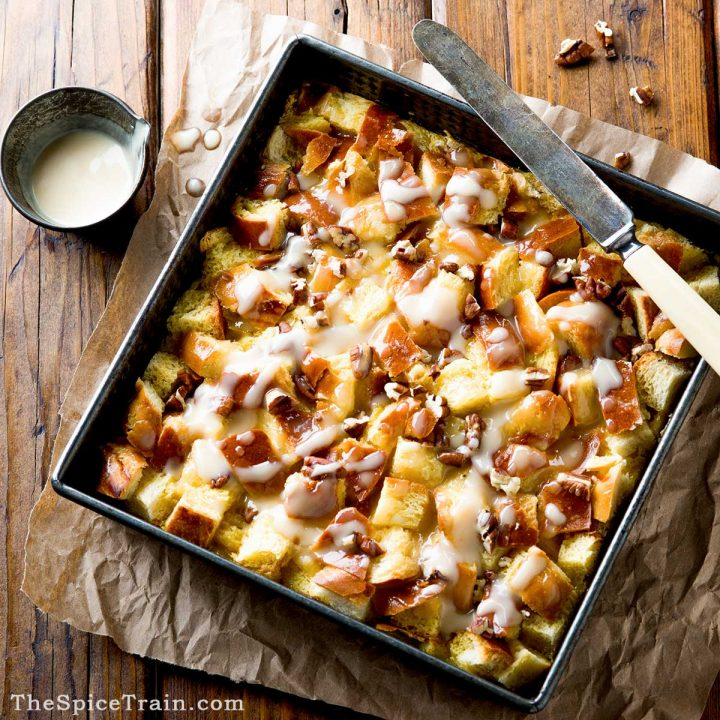 A square metal baking pan with baked bread pudding drizzled with maple cream sauce.