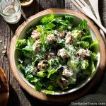A large bowl of chicken caesar salad along with a jar of dressing on a rustic wooden table.