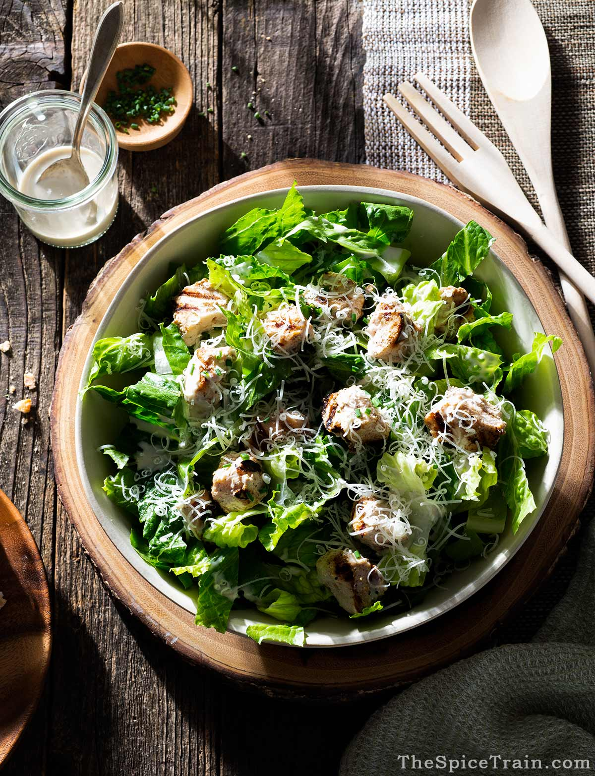 A large bowl of chicken caesar salad with a jar of dressing on a wood table.