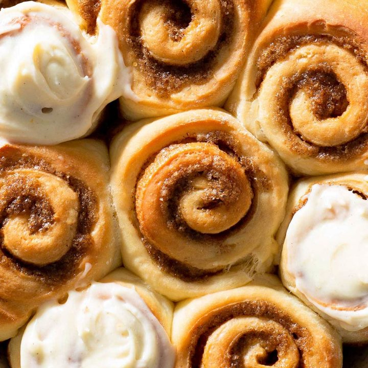 A closeup view of freshly baked cinnamon rolls with cream cheese frosting.