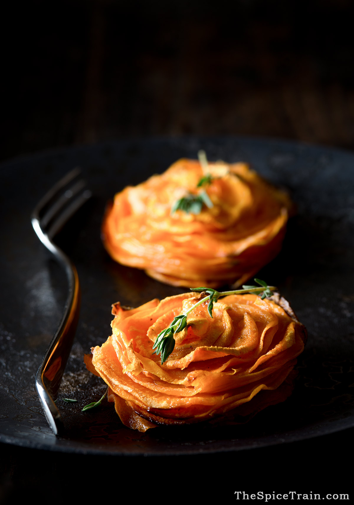 Two sweet potato stacks on a black plate.