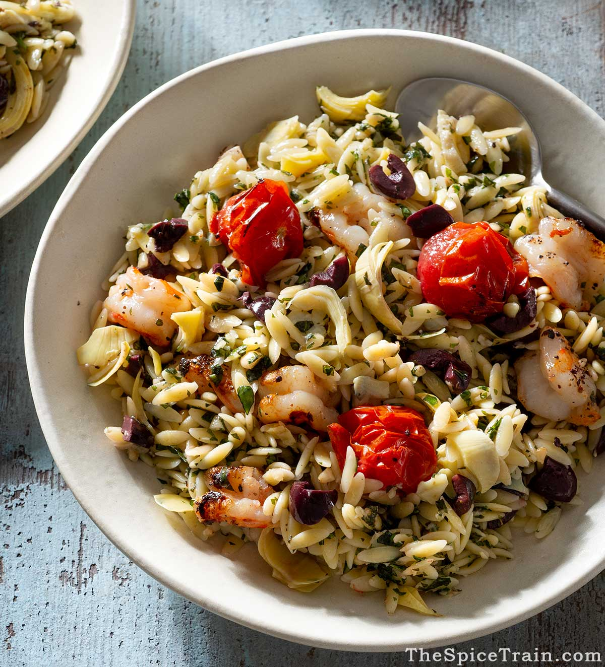 Shrimp orzo salad on a plate with a spoon.