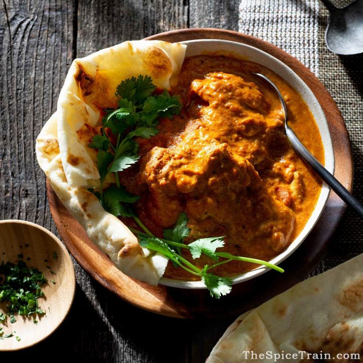 A bowl filled with Indian chicken curry, a side of naan bread and sprigs of fresh cilantro.