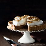 A s'mores chocolate mousse tart with a torched meringue topping on a cake stand.