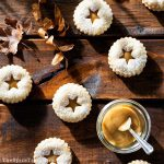 Shortbread Linzer cookies with dulce de leche filling on a wooden table.