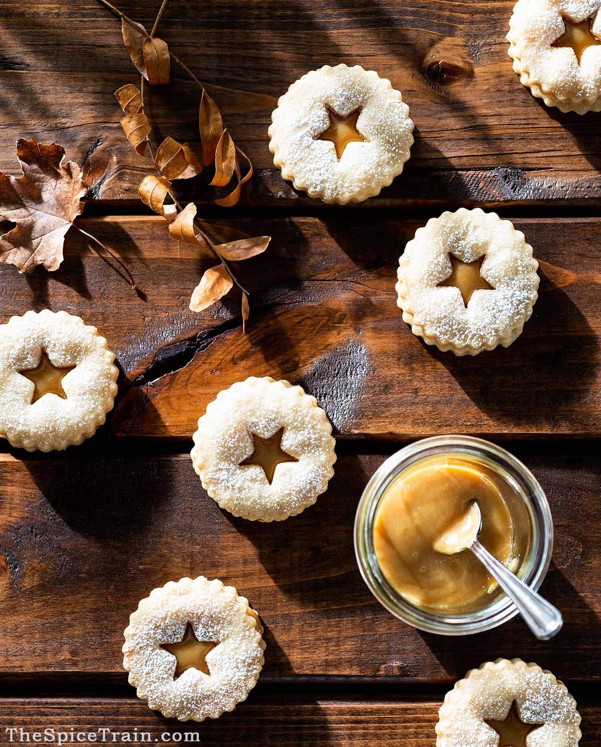 Shortbread Linzer cookies filled with dulce de leche on a wooden table.