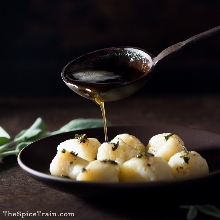 Gnocchi on a small plate being drizzled with a brown butter and sage sauce.