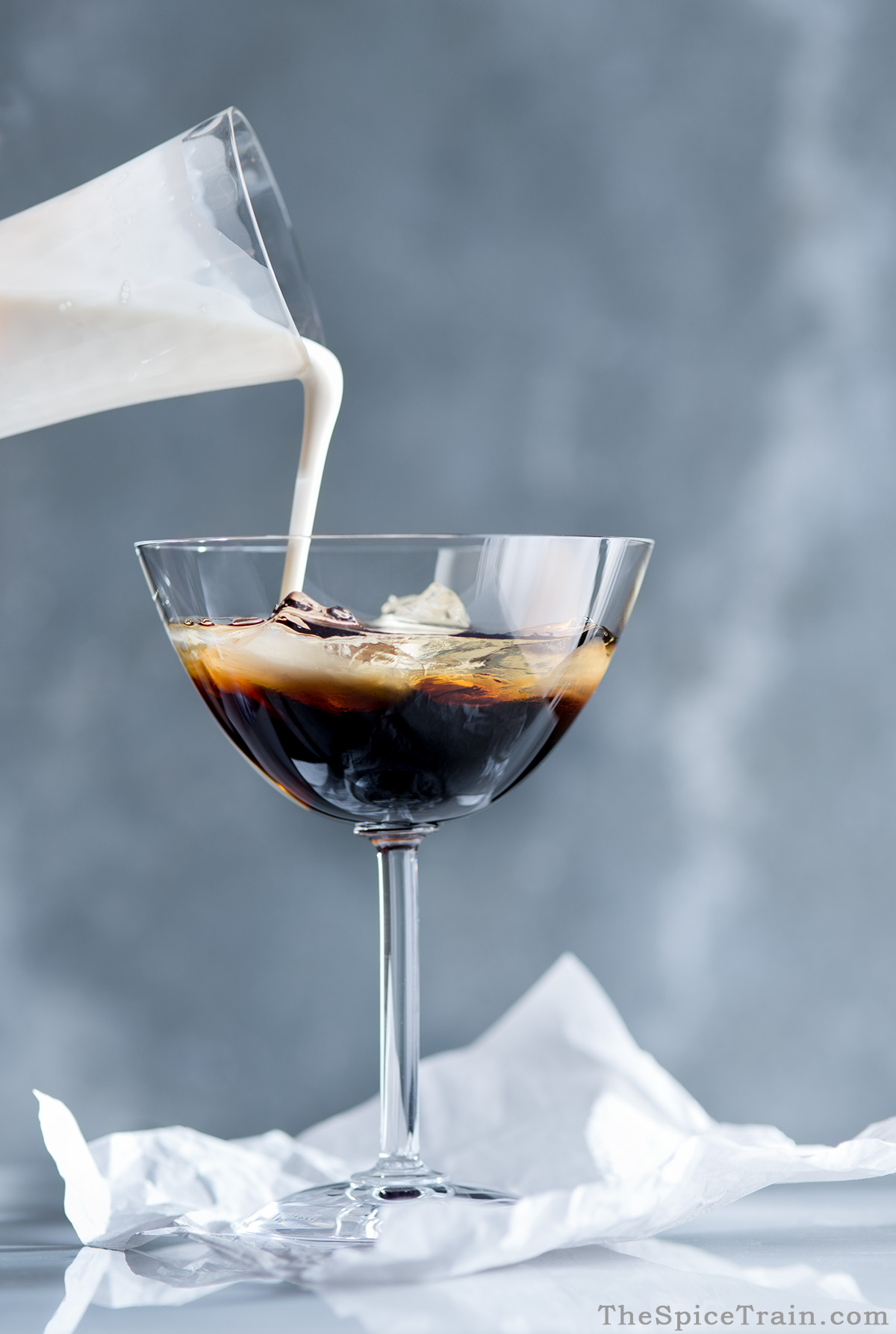 Cream being poured into a white Russian cocktail.