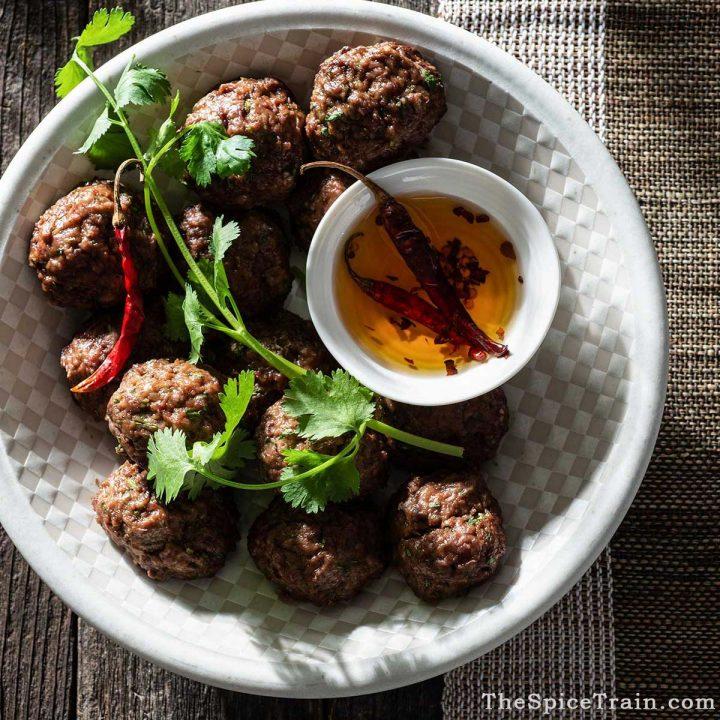 Asian meatballs on a plate, garnished with fresh cilantro.