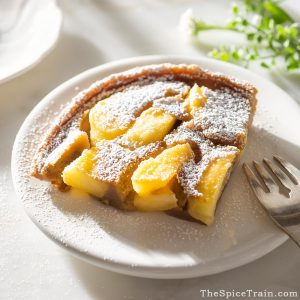 A slice of apple clafoutis on a small plate with a fork.