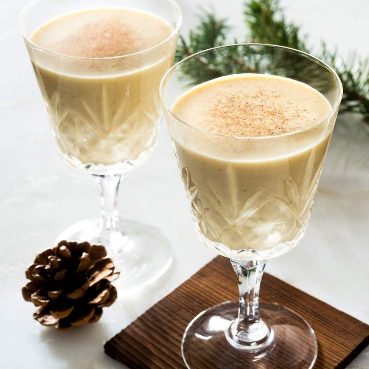 Two elegant glasses filled with eggnog in a festive setting.