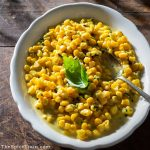 Curried corn with basil on a serving plate.