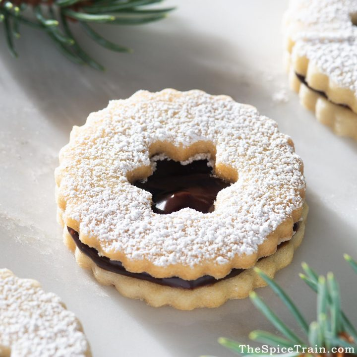 Closeup view of a linzer cookies filled with chocolate ganache.