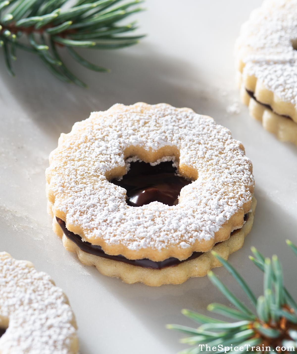 Closeup of a Linzer cookie filled with chocolate ganache.