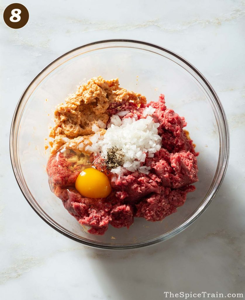 Raw meatball ingredients in a bowl.