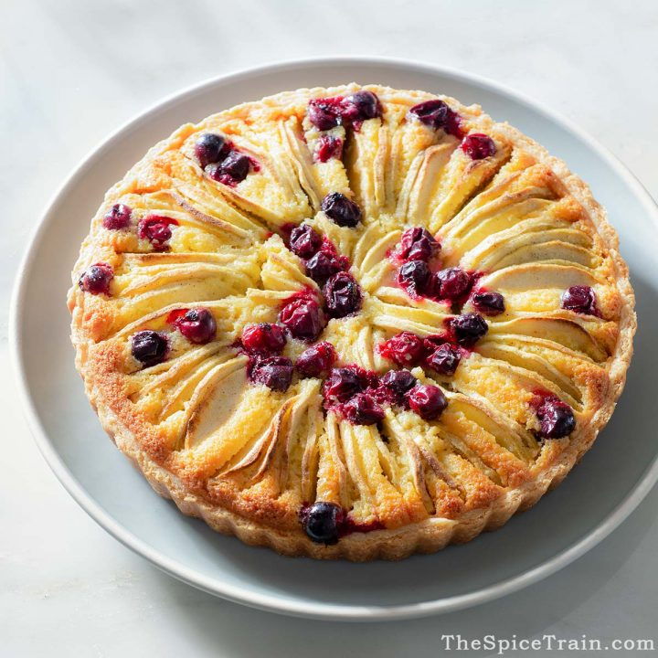A cranberry apple frangipane tart on a light blue plate.