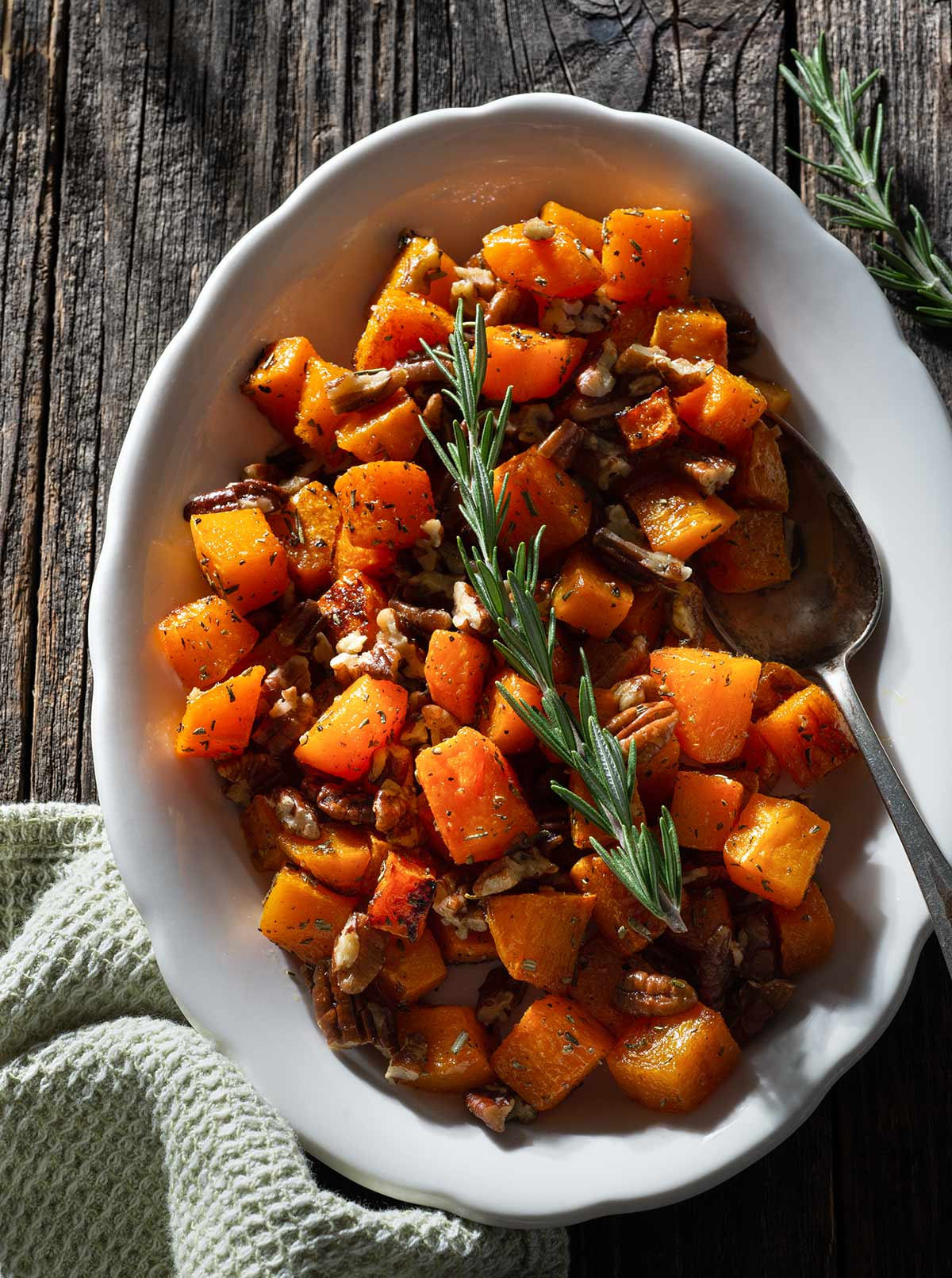 Roasted butternut squash with rosemary and pecans on a serving plate.