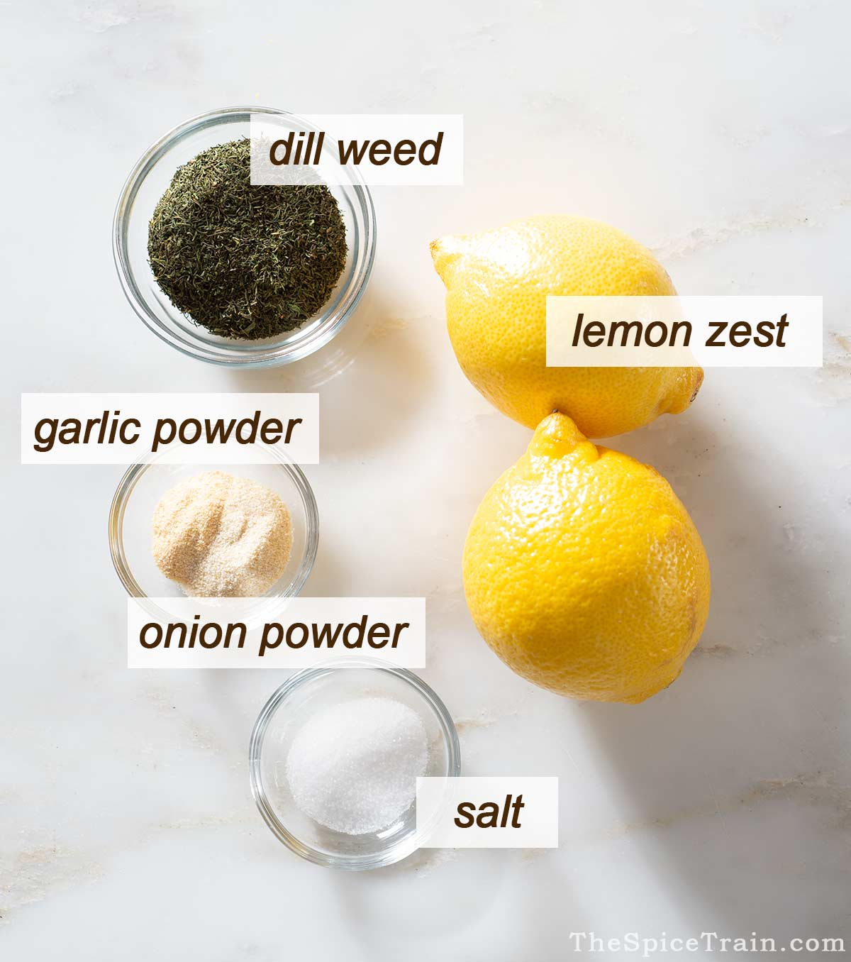 Lemons, dill, salt and garlic and onion powder on a kitchen counter.